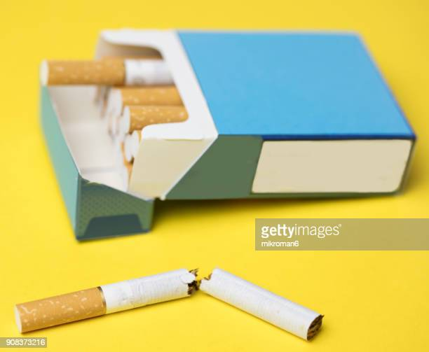 Breaking the habit. Cigarette box and cigarettes on yellow background