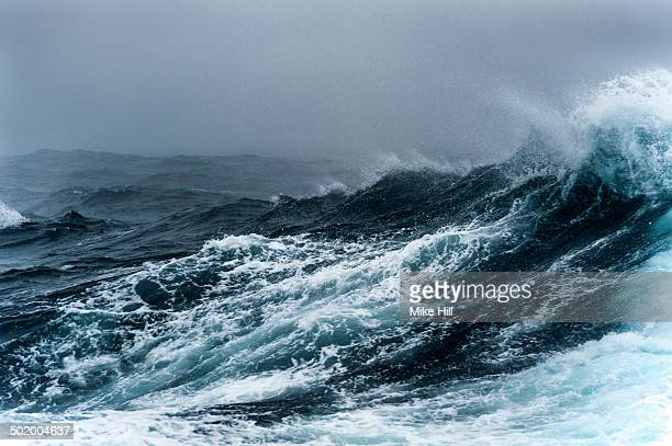 breaking wave on a rough sea against overcast sky - roh stock-fotos und bilder