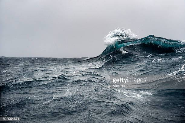 Breaking wave on a rough sea against overcast sky
