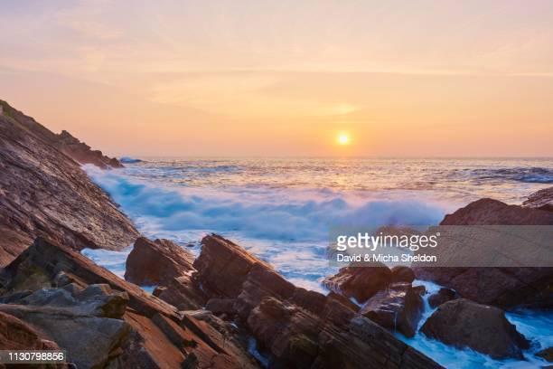 breaking waves at rocky coast at sunset, atlantik ocean, near hondarribia, basque country, spain - atlantik stock pictures, royalty-free photos & images