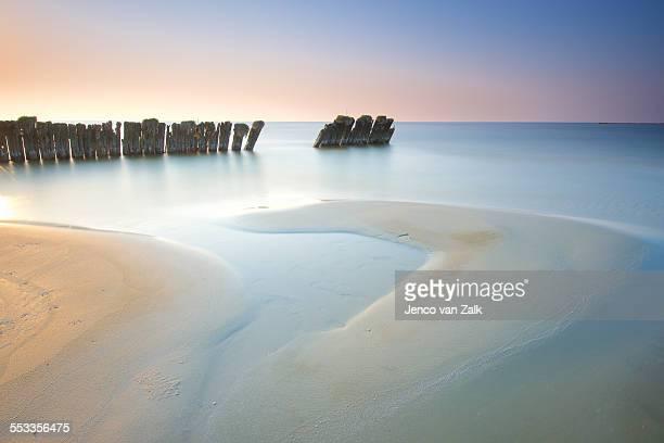 Breakwater and sandbar at sunset
