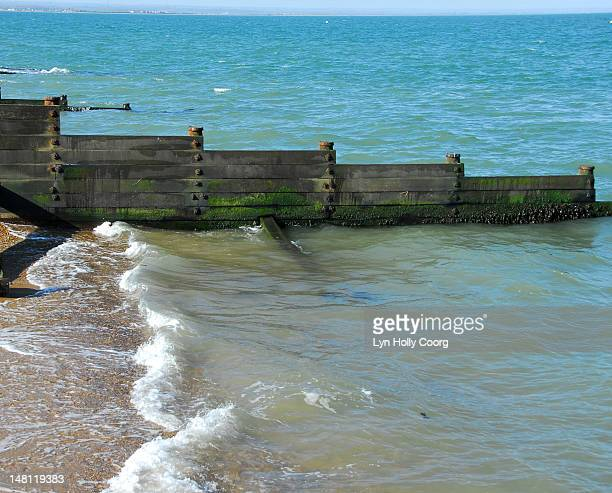 breakwater groynes on a beach with waves - lyn holly coorg stock pictures, royalty-free photos & images
