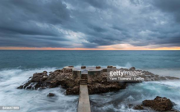 Breakwater On Beach Against Cloudy Sky During Sunset