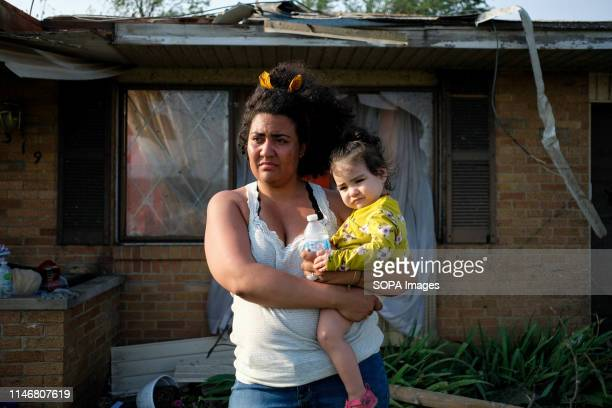 Breann holds her baby in front of their damaged house from the previous nights tornado that struck the area At least 1 person is dead and 12 injured...