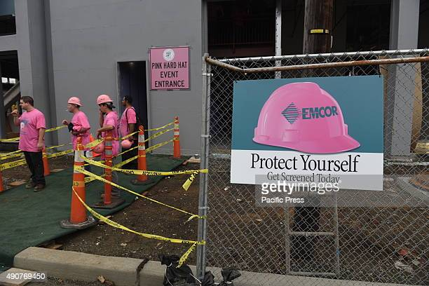 Breast cancer awareness sign outside construction site with pink clad workers in the background Executives and employees of Emcor/FG Manufacturing...