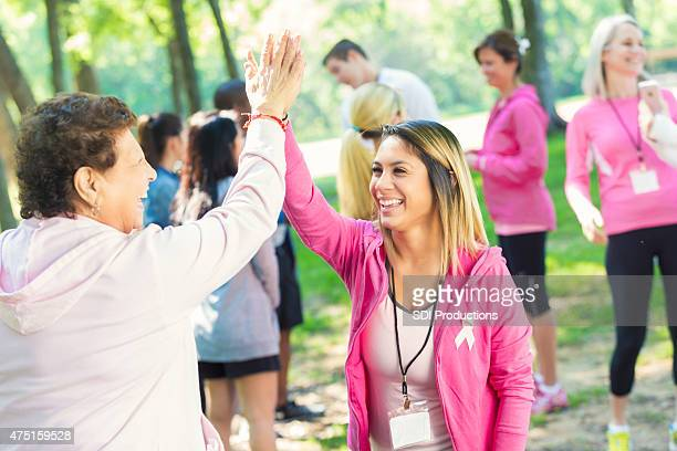 breast cancer survivor high fiving volunteer at charity race - social awareness symbol stock photos and pictures