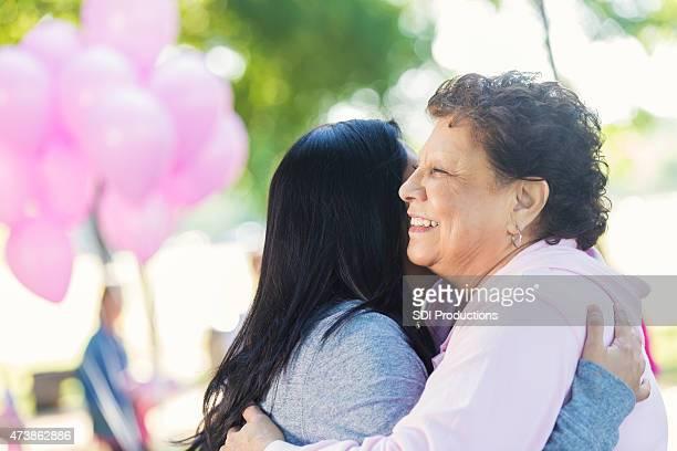 Breast cancer survivor hugging daughter after charity race
