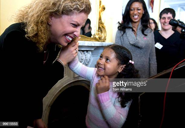 Breast cancer survivor Rep Debbie Wasserman Schultz DFla listens to a toy that tells stories given to her by Noelle KarmoWalsh daughter of breast...