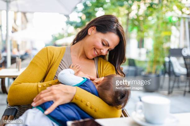 breast feeding in public place - breastfeeding stock pictures, royalty-free photos & images
