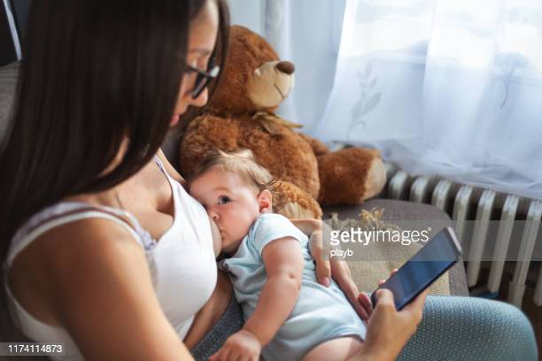 breastfeeding a baby while using phone - innocence stock pictures, royalty-free photos & images