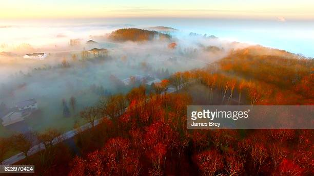 Breathtaking hilltop homes shrouded in Autumn fog at sunrise