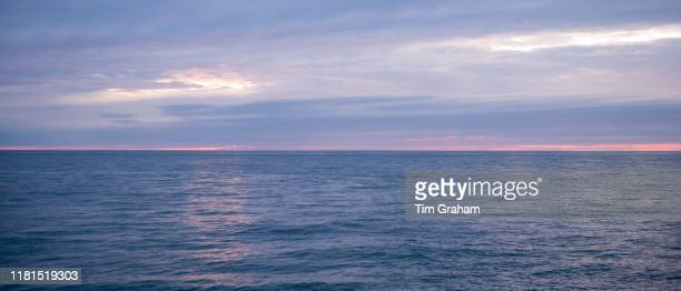 Breathtaking spectacular pastel colours of setting sun above the calm sea of the Atlantic Ocean in Wales United Kingdom