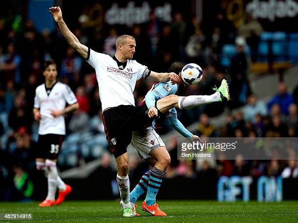 Brede Hangeland of Fulham battles with Grant Holt of Aston Villa during the Barclays Premier League match between Aston Villa and Fulham at Villa...
