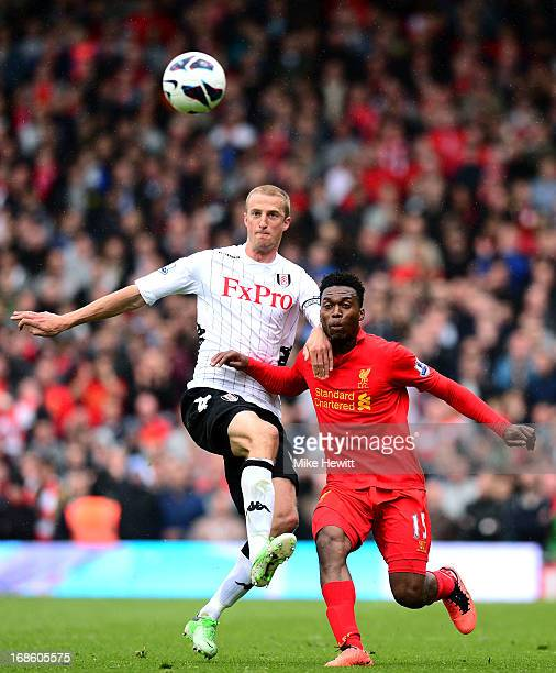 Brede Hangeland of Fulham clears the ball under pressure from Daniel Sturridge of Liverpool during the Barclays Premier League match between Fulham...
