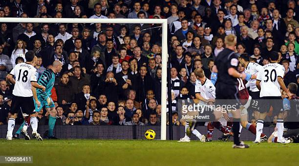 Brede Hangeland of Fulham heads home a last minute equaliser as goalkeeper Brad Friedel of Aston Villa can only watch during the Barclays Premier...