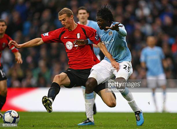 Brede Hangeland of Fulham holds off a challenge from Emmanuel Adebayor of Manchester City during the Barclays Premier League match between Manchester...