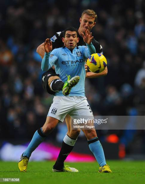 Brede Hangeland of Fulham in action with Carlos Tevez of Man City during the Barlcays Premier League match between Manchester City and Fulham at the...