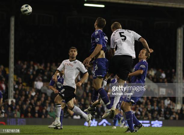 Brede Hangeland of Fulham rises above Gary Cahill to score his sides third goal during the Barclays Premier League match between Fulham and Bolton...