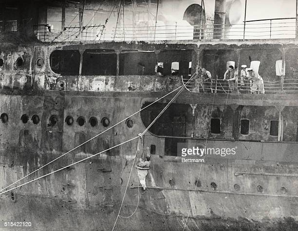 A breeches buoy shown reaching the hot sides of the SS Morro Castle as she lay on the beach Those men seeking bodies of the 200 victims of...