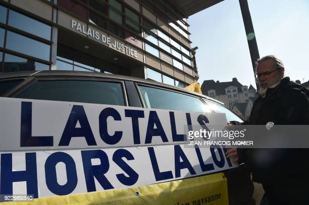 A breeder puts up a placard reading 'Lactalis unlawful' as French farmers demonstrate at the call of the Confederation Paysanne to ask the juduciary...