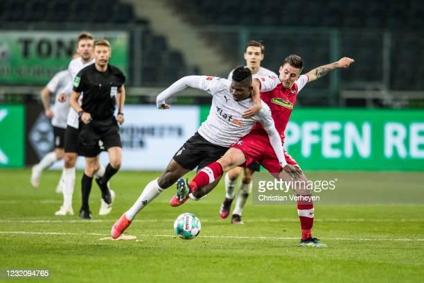 Breel Embolo of Borussia Moenchengladbach and Baptiste Santamaria of SC Freiburg battle for the ball during the Bundesliga match between Borussia...