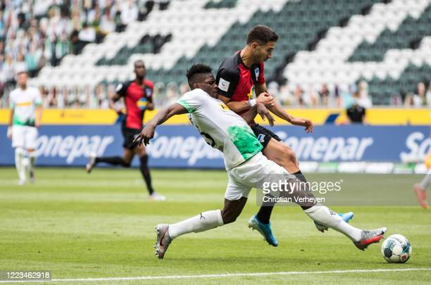 Breel Embolo of Borussia Moenchengladbach and Marko Grujic of Hertha BSC in action during the Bundesliga match between Borussia Moenchengladbach and...