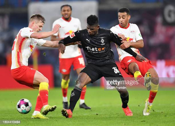 Breel Embolo of Borussia Moenchengladbach is challenged by Dani Olmo and Tyler Adams of RB Leipzig during the Bundesliga match between RB Leipzig and...