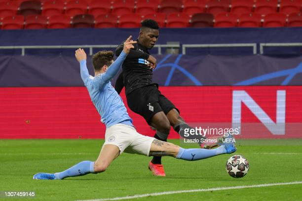 Breel Embolo of Borussia Moenchengladbach shoots whilst under pressure from John Stones of Manchester City during the UEFA Champions League Round of...