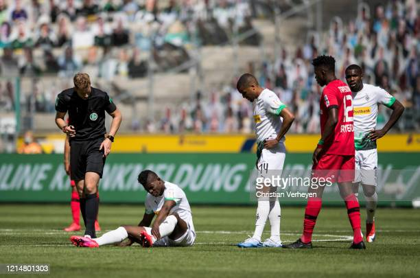 Breel Embolo of Borussia Moenchengladbach sitting on the pitch injured while Alassane Plea and Marcus Thuram of Borussia Moenchengladbach and Edmond...