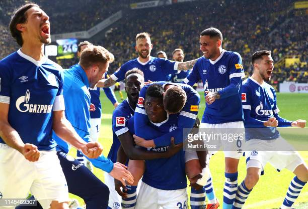 Breel Embolo of FC Schalke 04 celebrates with teammates after scoring his team's fourth goal during the Bundesliga match between Borussia Dortmund...