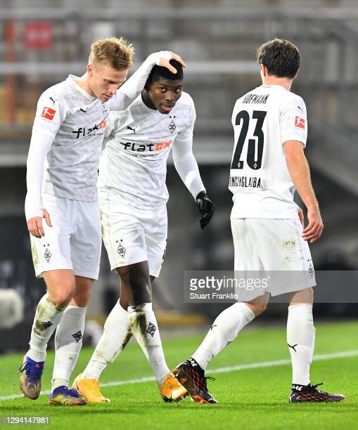 Breel Embolo of Moenchengladbach celebrates his team's first goal with teammates Oscar Wendt and Jonas Hofmann during the Bundesliga match between...
