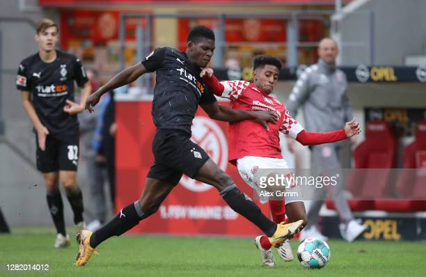 Breel Embolo of Moenchengladbach is challenged by Leandro Barreiro of Mainz during the Bundesliga match between 1 FSV Mainz 05 and Borussia...