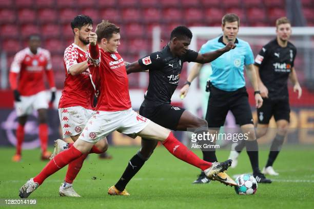 Breel Embolo of Moenchengladbach is challenged by Luca Kilian and Danny Latza of Mainz during the Bundesliga match between 1 FSV Mainz 05 and...