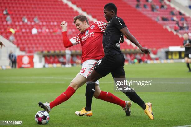 Breel Embolo of Moenchengladbach is challenged by Luca Kilian of Mainz during the Bundesliga match between 1 FSV Mainz 05 and Borussia...