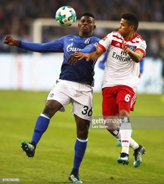 Breel Embolo of Schalke 04 is challenged by Douglas of Hamburger SV during the Bundesliga match between FC Schalke 04 and Hamburger SV at...