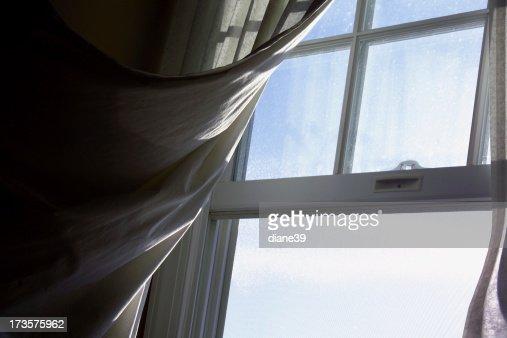 Breeze Blowing A Curtain Through An Open Window Stock