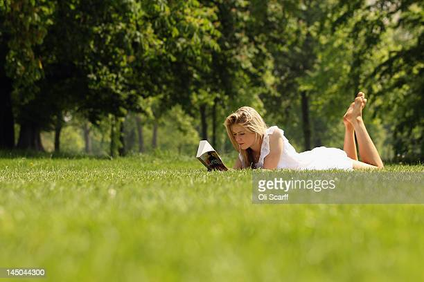 Breeze Burgess reads her book in the sunshine in Hyde Park on May 23 2012 in London England Following the high afternoon temperatures in the capital...