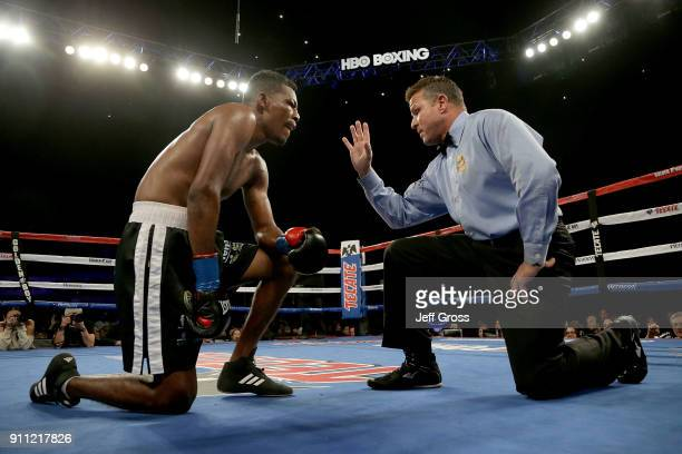 Breidis Prescott of Colombia receives a standing eight count after after he was knocked down by Marcelino Lopez of Argentina during their...
