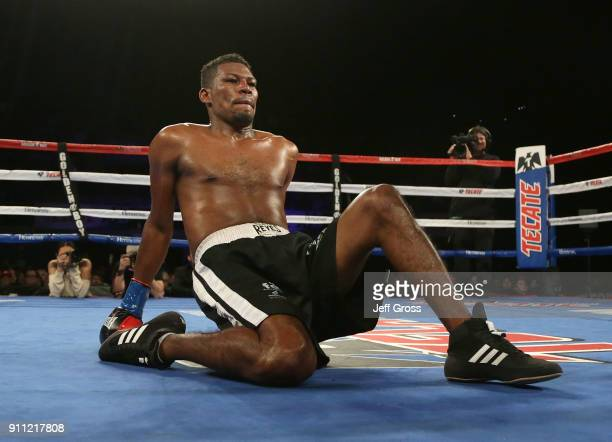 Breidis Prescott of Colombia struggles to get to his feet after being knocked down by Marcelino Lopez of Argentina during their welterweight bout at...