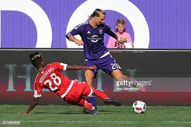 Brek Shea of Orlando City SC avoids a tackle from London Woodberry of New England Revolution during a MLS soccer match at the Orlando Citrus Bowl on...