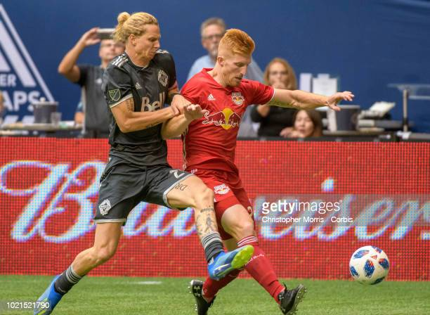 Brek Shea of Vancouver Whitecaps and Tim Parker of New York Red Bulls battle for the ball at BC Place on August 18 2018 in Vancouver Canada