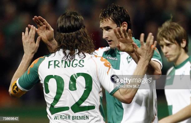 Werder Bremen's striker Miroslav Klose is congratulated by his teammates midfielder Torsten Frings and striker Aaron Hunt after scoring the 31...
