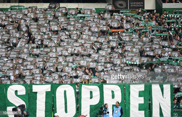 Bremen supporters hold flyers in protest prior to the German first division Bundesliga football match Werder Bremen v Hertha Berlin in Bremen...