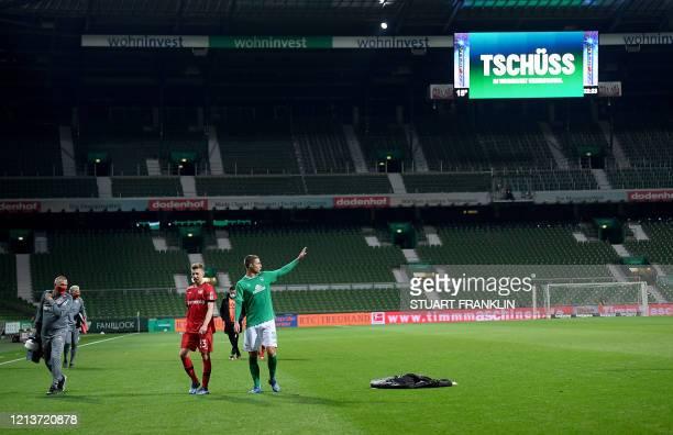 Bremen's Austrian forward Marco Friedl waves next to Leverkusen's German defender Mitchell Weiser after the German first division Bundesliga football...