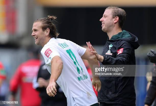 Bremen's German forward Niclas Fuellkrug is congratulated by Bremen's German head coach Florian Kohfeldt after scoring the 5-1 during the German...