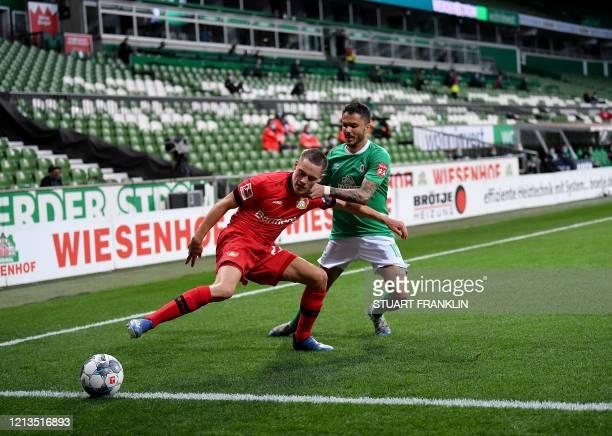Bremen's German midfielder Leonardo Bittencourt and Leverkusen's German forward Florian Wirtz vie for the ball during the German first division...