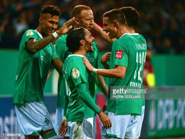 Bremen's German midfielder Leonardo Bittencourt celebrates scoring the 2-0 goal with his team-mates during the German Cup round of 16 football match...