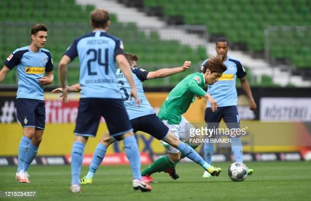 Bremen's Japanese forward Yuya Osako and Moenchengladbach's Christoph Kramer vie for the ball during the German first division Bundesliga football...