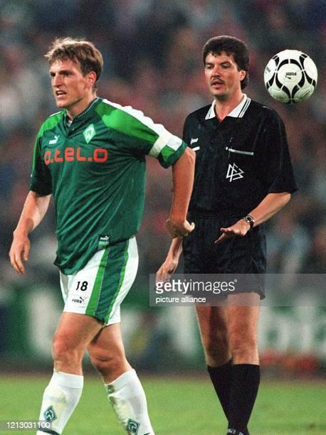 Bremens Mittelfeldspieler Andreas Herzog wirft vor den Augen von Schiedsrichter Herbert Fandel am 23.9.1997 im Frankfurter Waldstadion im...