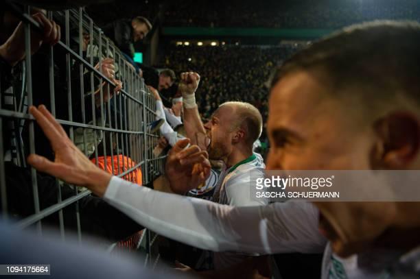 TOPSHOT Bremen's Player celebrates with their fans after the German Cup last 16 football match BVB Borussia Dortmund v Werder Bremen in Dortmund...